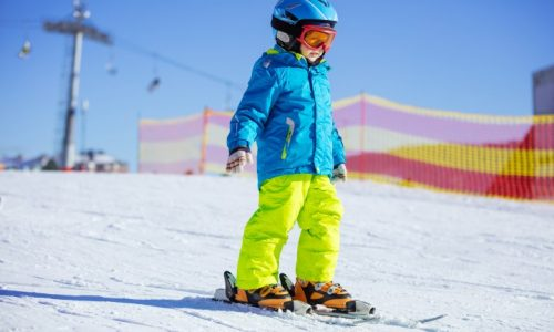 Little boy skiing downhill, wearing safety helmet and goggles